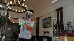 Seorang pekerja dengan mengenakan alat pelindung membersihkan pintu sebuah hotel yang dibuka kembali setelah penutupan selama ditutup selama tiga bulan akibat pandemi COVID-19 di Banda Aceh pada Rabu (15/7/2020). (Photo by CHAIDEER MAHYUDDIN / AFP)