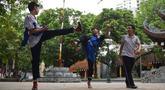 """Pemuda Vietnam memainkan permainan """"da cau"""" atau bulutangkis menggunakan bagian tubuh di dalam kompleks kuil Budha di Hanoi pada 25 Oktober 2019. Da Cau mirip dengan bulutangkis, tetapi tidak menggunakan raket untuk memukul kok, melainkan menggunakan setiap bagian tubuh.  (Nhac NGUYEN / AFP)"""