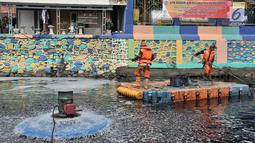 Petugas PPSU membersihkan sampah saat pengoperasian Nano Bubble dan Aerator di Kali Item, Jakarta, Kamis (2/8). Berbagai cara, dari pemberian oksigen melalui pengoperasian Nano Bubble dan Aerator hingga penyedotan 24 jam. (Merdeka.com/Iqbal S. Nugroho)