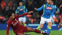 Bek Liverpool, Virgil Van Dijk, menekel striker Napoli, Dries Mertens, pada laga Liga Champions di Stadion Anfield, Liverpool, Selasa (11/12). Liverpool menang 1-0 atas Napoli. (AFP/Paul Ellis)