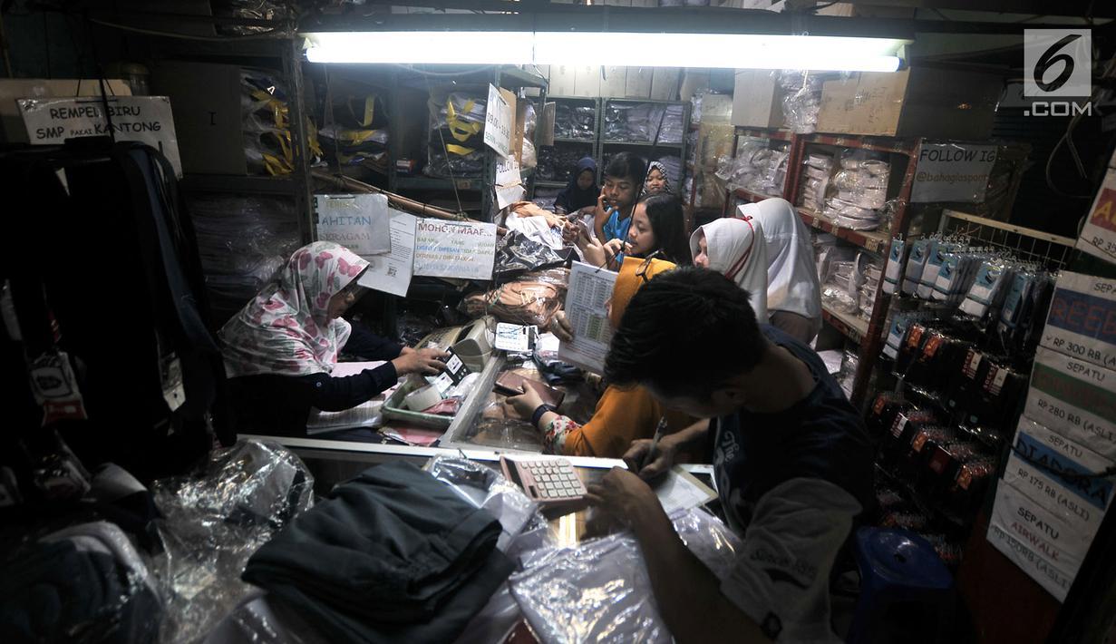 Pedagang melayani calon pembeli seragam sekolah saat berbelanja di salah satu toko di Pasar Sunan Giri, Jakarta, Selasa (3/7). Orangtua murid mulai berburu seragam sekolah untuk anak mereka jelang tahun ajaran baru 2018/2019. (Merdeka.com/Iqbal Nugroho)