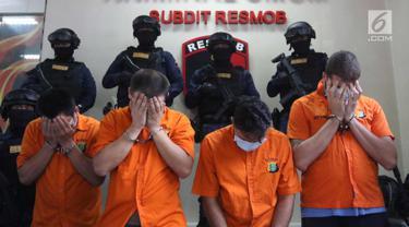 Empat WNA tersangka menutupi wajah saat pengungkapan tiga kasus pencurian data elektronik (Skimming) di Polda Metro Jaya, Jakarta, Selasa (4/3). Empat tersangka tersebut berhasil diamankan Ditreskrimum Polda Metro Jaya. (Liputan6.com/Arya Manggala)