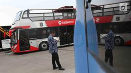 Petugas berada di dekat bus transjakarta yang akan digunakan untuk pawai kemenangan tim Persija Jakarta di kantor PT Transjakarta, Cawang, Kamis (13/12). Bus tersebut akan digunakan untuk pawai kemenangan Persija.(Www.sulawesita.com)