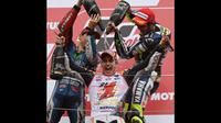Pembalap Yamaha MotoGP, Jorge Lorenzo (kiri) dan Valentino Rossi mengguyurkan sampanye ke Marc Marquez di podium kemenangan di Sirkuit Motegi, Jepang, (12/10/2014). (AFP PHOTO/Toshifumi Kitamura)