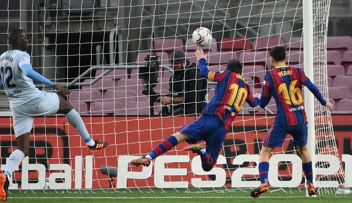 Striker Barcelona, Lionel Messi (kedua dari kanan), mencetak gol pertama timnya lewat sundulan kepala ke gawang Valencia dalam laga lanjutan Liga Spanyol 2020/21 di Camp Nou Stadium, Barcelona, Sabtu (19/12/2020). Barcelona bermain imbang 2-2 dengan Valencia. (AFP/Lluis Gene)