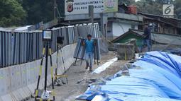 Pekerja melintasi area lokasi longsor di kawasan Ciloto, Cianjur, Jawa Barat, Sabtu (31/3). Area longsor mulai diperbaiki oleh pihak terkait. (Liputan6.com/Helmi Fithriansyah)