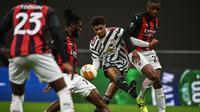 Striker Manchester United, Marcus Rashford (tengah) dijepit dua pemain AC Milan, Franck Kessie dan Pierre Kalulu dalam laga leg kedua babak 16 besar Liga Europa 2020/2021 di San Siro Stadium, Millan, Kamis (18/3/2021). Manchester United menang 1-0 atas AC Milan. (AFP/Marco Bertorello)