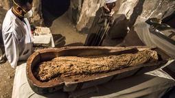 Arkeolog berdiri dekat mumi wanita bernama Thuya dalam sarkofagus di Luxor, Meisr, Sabtu (24/11). Sarkopafus itu adalah salah satu dari dua sarkofagus yang ditemukan awal bulan ini, dalam sebuah misi pencarian oleh peneliti Prancis. (Khaled DESOUKI/AFP)