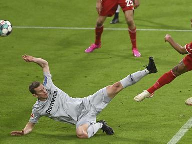 Striker Bayern Munich, Eric Maxim-Choupo Moting (kanan) melepaskan tendangan yang berbuah gol pertama timnya ke gawang Bayer Leverkusen dalam laga lanjutan Liga Jerman 2020/2021 pekan ke-30 di Allianz Arena, Munich, Selasa (20/4/2021). Bayern Munich menang 2-0. (AP/Christof Stache/Pool)
