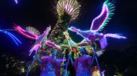 Dua orang wanita dari rombongan Tian Eng Dragon and Lion Dance Centre tampil membawakan tarian phoenix yang dihiasi dengan lampu warna-warni di Gardens by the Bay, Singapura (4/2). (AFP/Roslan Rahman)
