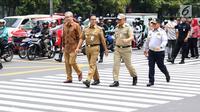 Gubernur DKI Jakarta Anies Baswedan (dua kiri) menyeberangi pelican crossing di Halte Transjakarta BI, Jakarta, Selasa (4/9). Pelican crossing diharap membuat warga memiliki kesempatan sama dalam menikmati layanan publik. (Liputan6.com/Immanuel Antonius)