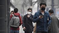 Sejumlah warga mengenakan masker wajah berjalan menyusuri jalan pada hari yang tercemar polusi di Beijing, China (2/4). (AFP Photo/Fred Dufour)
