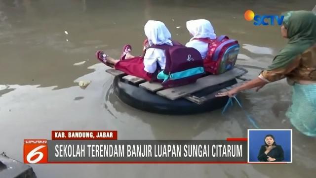 Banjir yang menerjang kawasan Kabupaten Bandung belum juga surut. Siswa SD terpaksa berangkat sekolah menggunakan rakit dari ban bekas.