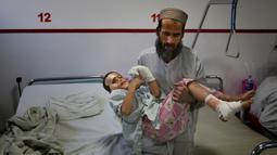 Ismatullah membawa putranya Eimal (9) yang kehilangan mata kanan dan beberapa jari tangannya dalam ledakan ranjau darat di Pusat Bedah Darurat untuk Korban Perang Sipil di Kabul, Afghanistan, Kamis (12/12/2019). (AP Photo/Altaf Qadri)