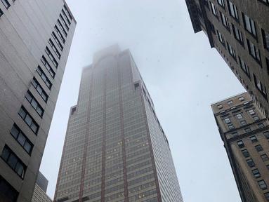 Asap mengepul saat sebuah helikopter menabrak gedung pencakar langit di pusat Manhattan, New York, Amerika Serikat, Senin (10/6/2019). Seorang pilot dilaporkan tewas dalam insiden tersebut. (AP Photo/Mark Lennihan)
