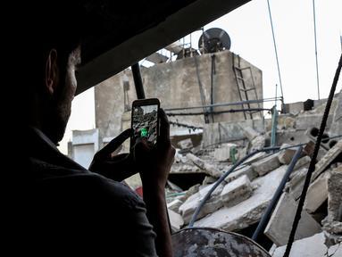 Seorang gamer Suriah menggunakan aplikasi Pokemon Go di ponselnya untuk mencari Pokemons di antara puing-puing di kota Douma, Damaskus (23/7). (AFP PHOTO / Sameer Al-Doumy)
