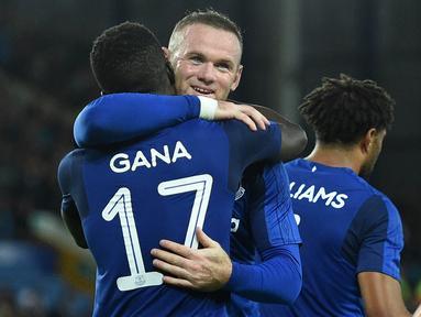 Striker Everton, Wayne Rooney, memeluk rekannya, Idrissa Gueye, yang berhasil mencetak gol ke gawang  Hajduk Split pada leg I play-off Liga Europa di Stadion Goodison Park, Jumat (18/8/20127). Everton menang 2-0 atas Hajduk Split. (AFP/Oli Scarff)