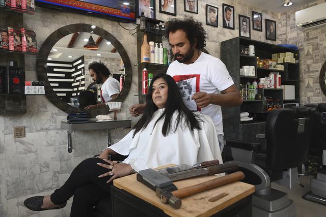 Dalam gambar pada 8 April 2021, tukang cukur Pakistan Ali Abbas memeriksa rambut pelanggan setelah memotongnya dengan pisau daging dan palu di Lahore. Berharap membuktikan kemampuannya dalam persaingan, Ali Abbas mengandalkan berbagai alat yang tidak biasa untuk melatih keahliannya. (Arif ALI/AFP)