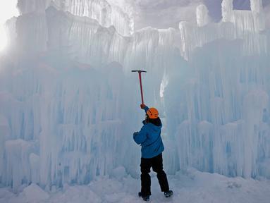 Seorang pekerja memahat dinding es saat mebuat kastel atau Istana Es di Midway, Utah (27/12). Nantinya pengunjung akan dapat menikmati Istana Es yang terdiri dari labirin, ngarai atau lembah, terowongan dan air mancur. (AP/Rick Bowmer)