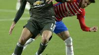 Striker Manchester United, Mason Greenwood (depan) berusaha melepaskan diri dari penjagaan pemain Granada dalam lanjutan Liga Europa 2020/2021, Jumat (9/4/2021) dini hari WIB. (CRISTINA QUICLER / AFP)