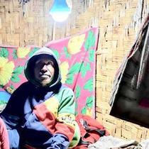 Warga duduk di bawah lampu listrik di Distrik Puldama, Kabupaten Yahukimo, Provinsi Papua. Jelang HUT ke-73 RI, untuk pertama kalinya warga Puldama menikmati lampu listrik di rumah mereka.(Www.sulawesita.com)