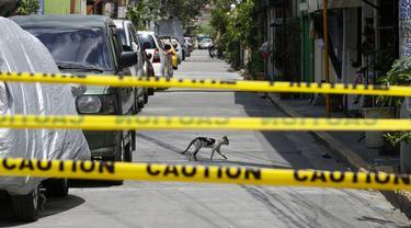 "Seekor kucing melintasi jalan kosong di desa yang dikunci di Manila  (11/3/2021). Ibukota Filipina menempatkan dua desa, dua hotel diisolasi dan polisi telah memperingatkan agar tidak berciuman dan ""bermesraan kasih sayang di depan publik"" setelah lonjakan infeksi Covid-19. (AP Photo/Aaron Favila)"