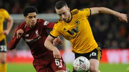 Pemain Liverpool, Ki-Jana Hoever merebut bola dari pemain  Wolverhampton Wanderers, Diogo Jota pada laga putaran ketiga Piala FA di Molineux Stadium, Senin (7/1). Liverpool tersingkir dari Piala FA setelah takluk 1-2 dari Wolverhampton. (AP/Rui Vieira)