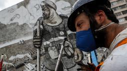 "Seniman Thiago Mundano berpose di samping muralnya ""The Forest Brigadir"" dari abu kebakaran hutan Amazon yang menutupi kompleks apartemen di Sao Paulo, Jumat (15/10/2021). Mural bergambar petugas damkar yang berdiri di tengah peristiwa deforestasi, kebakaran, dan hewan mati. (AP/Marcelo Chello)"