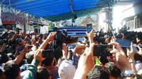 Mobil jenazah dan rombongan keluarga terpidana mati Freddy Budiman ditunggu warga di sepanjang jalan kawasan Krembangan Baru, Surabaya, Jawa Timur. (Liputan6.com/Dhimas Prasaja)