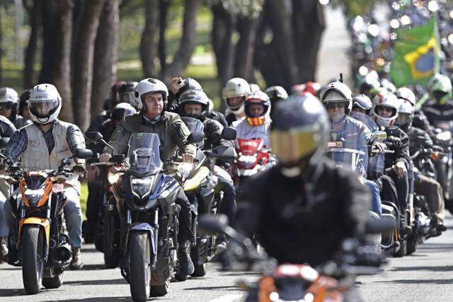 Presiden Brasil Jair Bolsonaro (kedua kiri) melakukan tur sepeda motor dengan para pendukung di Brasilia, di tengah pandemi corona pada Minggu (9/5/2021). Bolsonaro memimpin ratusan pengendara motor melakukan perjalanan mengelilingi ibu kota Brasil untuk memperingati Hari Ibu (AP Photo/Eraldo Peres)