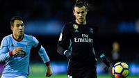 Pemain Real Madrid, Gareth Bale dan bek Celta Vigo, Hugo Mallo berebut bola pada pertandingan pekan ke-18 La Liga kontra Celta Vigo di Estadio de Balaidos, Minggu (7/1). Sempat unggul, Madrid akhirnya harus puas dengan skor akhir 2-2. (MIGUEL RIOPA/AFP)