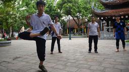 "Pemuda Vietnam memainkan permainan ""da cau"" atau bulutangkis menggunakan bagian tubuh di dalam kompleks kuil Budha di Hanoi pada 25 Oktober 2019. Pemain berusaha menjaga agar kok tidak menyentuh tanah dengan menggunakan bagian tubuh selain tangan. (Nhac NGUYEN / AFP)"