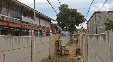 Warga memanjat tembok untuk memasuki rumahnya di kawasan Ciledug, Kota Tangerang, Banten, Senin (15/3/2021). Tembok beton sepanjang 300 meter dengan tinggi 2 meter serta dipasang kawat duri itu menutup akses menuju rumah dan tempat usaha milik warga. (Liputan6.com/Herman Zakharia)