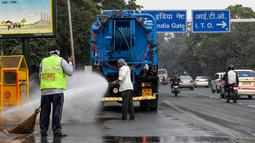 Petugas menyemprotkan air ke pohon-pohon untuk mengurangi polusi udara di pinggir jalan New Delhi, Rabu (6/11/2019). Tingkat polusi udara di Ibu Kota India itu kian memburuk, hingga mengancam kesehatan masyarakat. (Photo by Prakash SINGH / AFP)