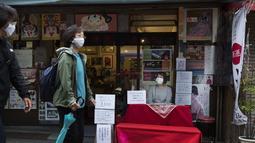 Seorang peramal yang menyebut dirinya Buchiko menunggu pelanggan saat orang-orang berjalan melalui jalan perbelanjaan di Tokyo (15/10/2020). Ibukota Jepang mengonfirmasi lebih dari 280 kasus virus korona baru pada hari Kamis. (AP Photo/Hiro Komae)