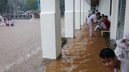 Banjir yang disebabkan hujan berkepanjangan di ibukota itu membuat sejumlah sekolah memulangkan anak didiknya lebih awal, Jakarta, Senin (9/2/2015). (Antara Foto/Fanny Octavianus)