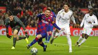 Striker Barcelona, Lionel Messi, berusaha menembus pertahanan Real Madrid pada laga La Liga 2019 di Stadion Camp Nou, Rabu (18/12). Kedua tim bermain imbang 0-0. (AP/Emilio Morenatti)