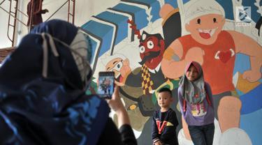 Anak-anak berpose di depan mural Wajah Baru Jakarta di terowongan Jalan Kendal, Jakarta, Kamis (20/6/2019).  Mural tersebut dibuat dalam rangka menyambut HUT ke-492 DKI Jakarta sekaligus mempercantik lingkungan. (merdeka.com/Iqbal S. Nugroho)