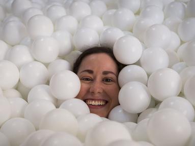 Seorang wanita tersenyum saat tenggelam dalam kolam bola putih di kantor SoHo, New York City, Selasa (25/8/2015). Tempat ini dibuat agar para karyawan dapat bermain dan dapat menhasilkan sesuatu yang kreatif. (REUTERS/Mike Segar)