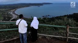 Wisatawan memandangi Teluk Ciletuh dari Puncak Darma Kawasan Geopark Ciletuh, Sukabumi, Sabtu (23/6). Kawasan yang dikenal sebagai salah satu taman batu tertua di Pulau Jawa ini resmi menyandang status UNESCO Global Geopark. (Merdeka.com/Arie Basuki)