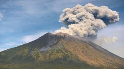 Gunung Agung mengeluarkan asap bercampur abu vulkanis terlihat dari desa Tulamben, Karangasem, Bali, Selasa (3/7). Walau terus mengalami letusan hampir sepekan terakhir, Gunung Agung masih berada pada status level III (siaga). (AFP/SONNY TUMBELAKA)