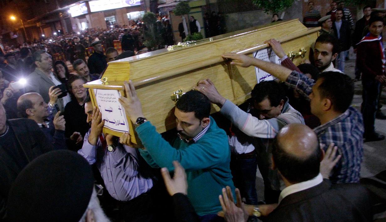 Umat Kristen Mesir menggotong peti jenazah korban serangan bom di Gereja Koptik St. George, Kota Tanta, utara Kairo, Minggu (9/4). Prosesi pemakaman digelar bagi 27 korban serangan teror bom yang terjadi tepat pada perayaan Minggu Palma itu (STRINGER/AFP)