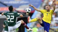 Gelandang Swedia, Sebastian Larsson (kanan) berusaha menyongsong bola dari kejaran pemain Meksiko, Hirving Lozano di Yekaterinburg Arena, Rabu (27/6/2018) pada matchday ketiga Piala Dunia 2018. (AP Photo/Martin Meissner)