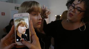 Model saat dirias wajahnya di belakang panggung sebelum tampil membawakan busana koleksi Beira selama Sao Paulo Fashion Week di Sao Paulo, Brasil (16/10/2019). SPFW ke-48 akan berlangsung hingga 18 Oktober.  (AP Photo / Nelson Antoine)