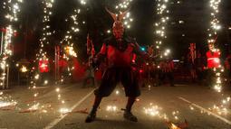 Peserta bersuka ria ambil bagian dalam festival tradisional Correfoc di Palma de Mallorca, Spanyol, Senin (21/1). Para peserta berkostum setan dan iblis berjalan-jalan sambil menakuti orang-orang dengan api dan kembang api. (JAIME REINA/AFP)