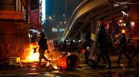 Polisi antihuru-hara tiba setelah demonstran membakar sampah di Hong Kong, Minggu (29/9/2019). Demonstrasi pada akhir pekan ini sendiri digelar beberapa hari menjelang perayaan kemerdekaan China. (AP Photo/Vincent Yu)
