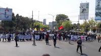 mahasiswa dari berbagai perguruan tinggi di Solo dan sekitarnya turun ke jalan menuntut pemerintah dan DPR menunda pengesahan RKUHP, penyelesaian masalah kebakaran hutan, hingga protes pelemahan UU KPK, serta penuntasan kasus Papua. (Solopos/ Nicolaus)