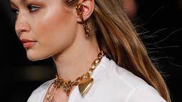 Model Gigi Hadid memperagakan busana koleksi Versace Pre-Fall 2019 di New York (2/12). Gigi Hadid tampil dengan berbagai kalung dan pin saat berjalan di atas catwalk. (AFP Photo/JP Yim)