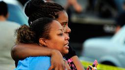 Salah satu keluarga korban penikaman menangis saat menyaksikan petugas melakukan penyelidikan di Louisiana, AS, Rabu (26/8/2015). Tersangka penikaman ditangkap satu jam kejadian. (REUTERS/Leslie Westbrook)
