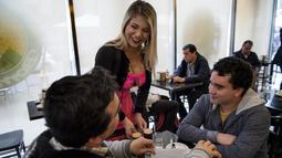 "Pramusaji membawa minuman pada pelanggan di kedai kopi ""Cafe con Piernas"", Santiago, Chile, 26 September 2018. Seiring dengan banyaknya turis pria kesana, kedai kopi inipun kian sering menjadi topik pembicaraan di kalangan traveler. (Martin BERNETTI/AFP)"